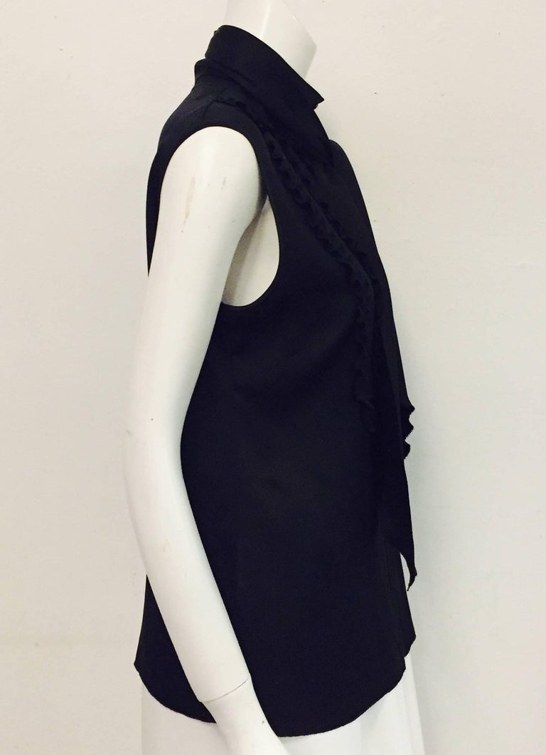This charming Chanel black silk sleeveless tuxedo style top takes the top hat, pun intended!   Three ruffles on each side of the blouse meeting at the center of blouse with hidden closure and 9 Chanel logo buttons.  Possesses an up collar with 3