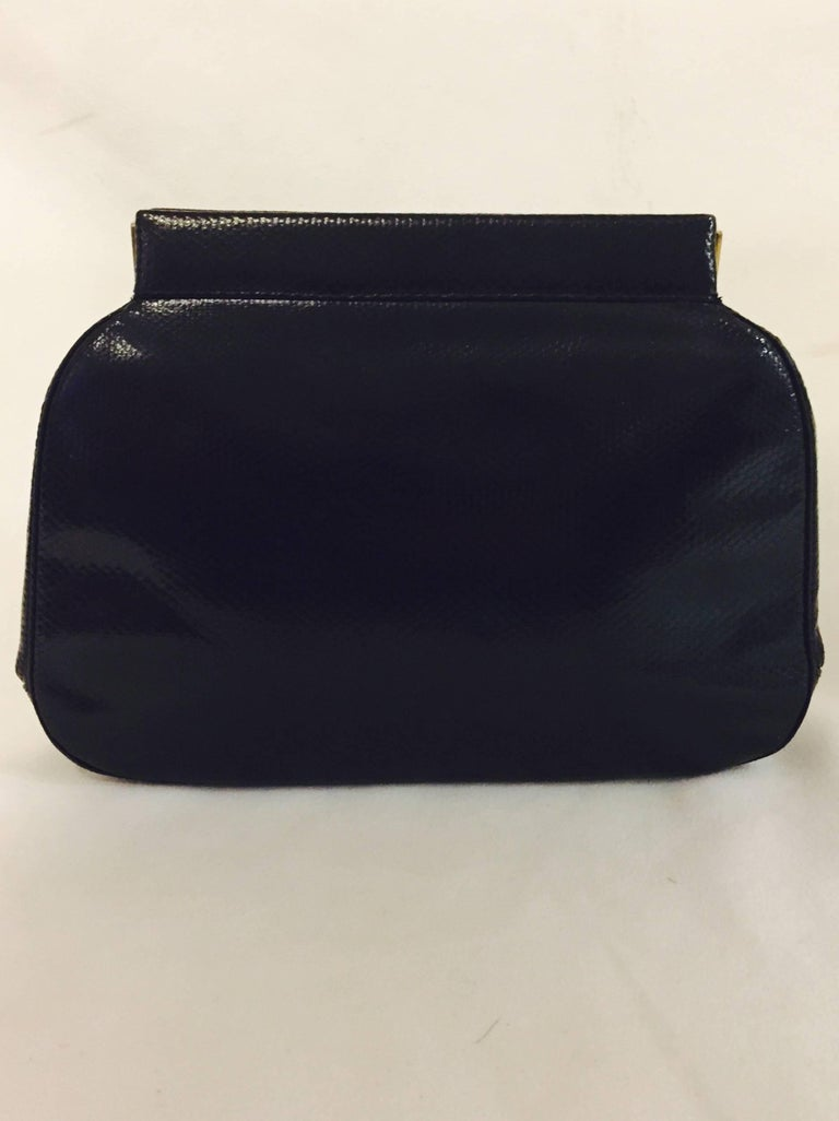 Judith Leiber evening bag creation features genuine black lizard with tonal top stitching.   This timeless frame bag has distinctive semi precious stones decoration at closure.  Optional lizard skin strap effortlessly converts this clutch to