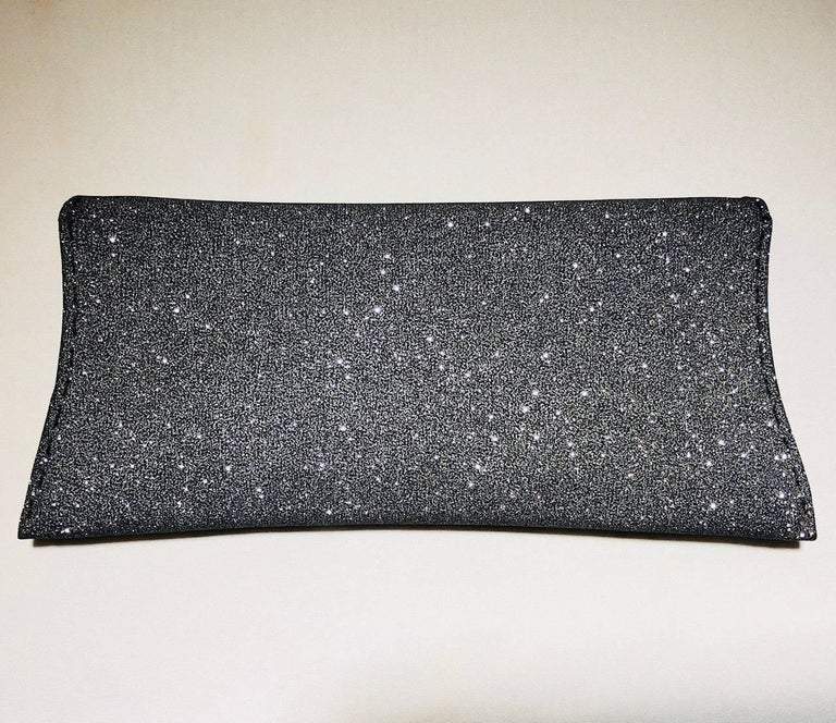 VBH  dark silver sparkle Manila clutch with overlay push through closure.  The interior is lined in grey suede with one small slit pocket.  Pick stitch detailing can be found around the bag in black thread.  Three metal studs at front closure.  In