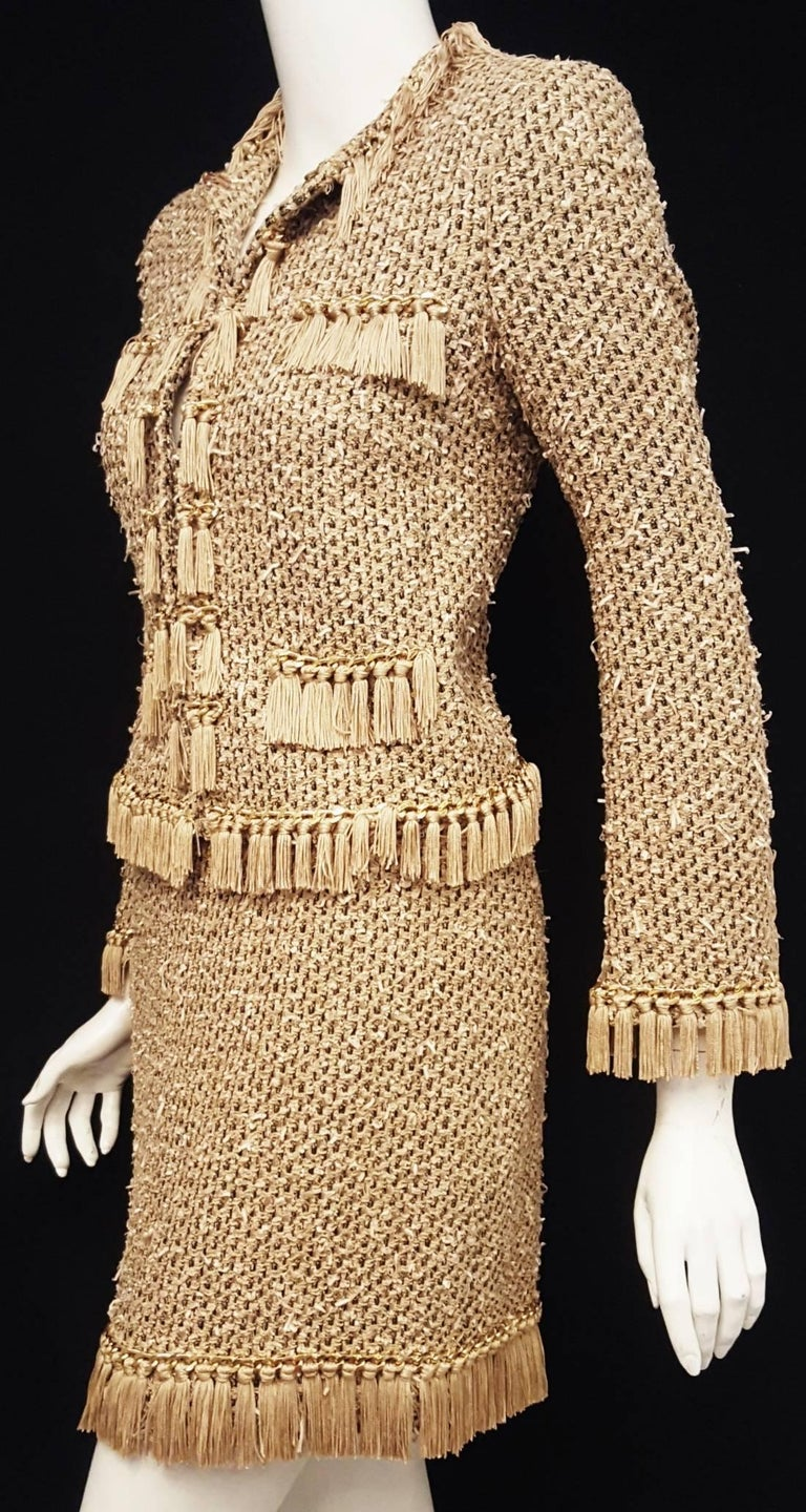 Moschino taupe, beige and black suit with tan fringe on jacket and skirt and a shiny gold tone chain is intricately decorated.  The fabric has woven into it tiny ribbons in ivory that are gently distressed giving the fabric a more textured look.
