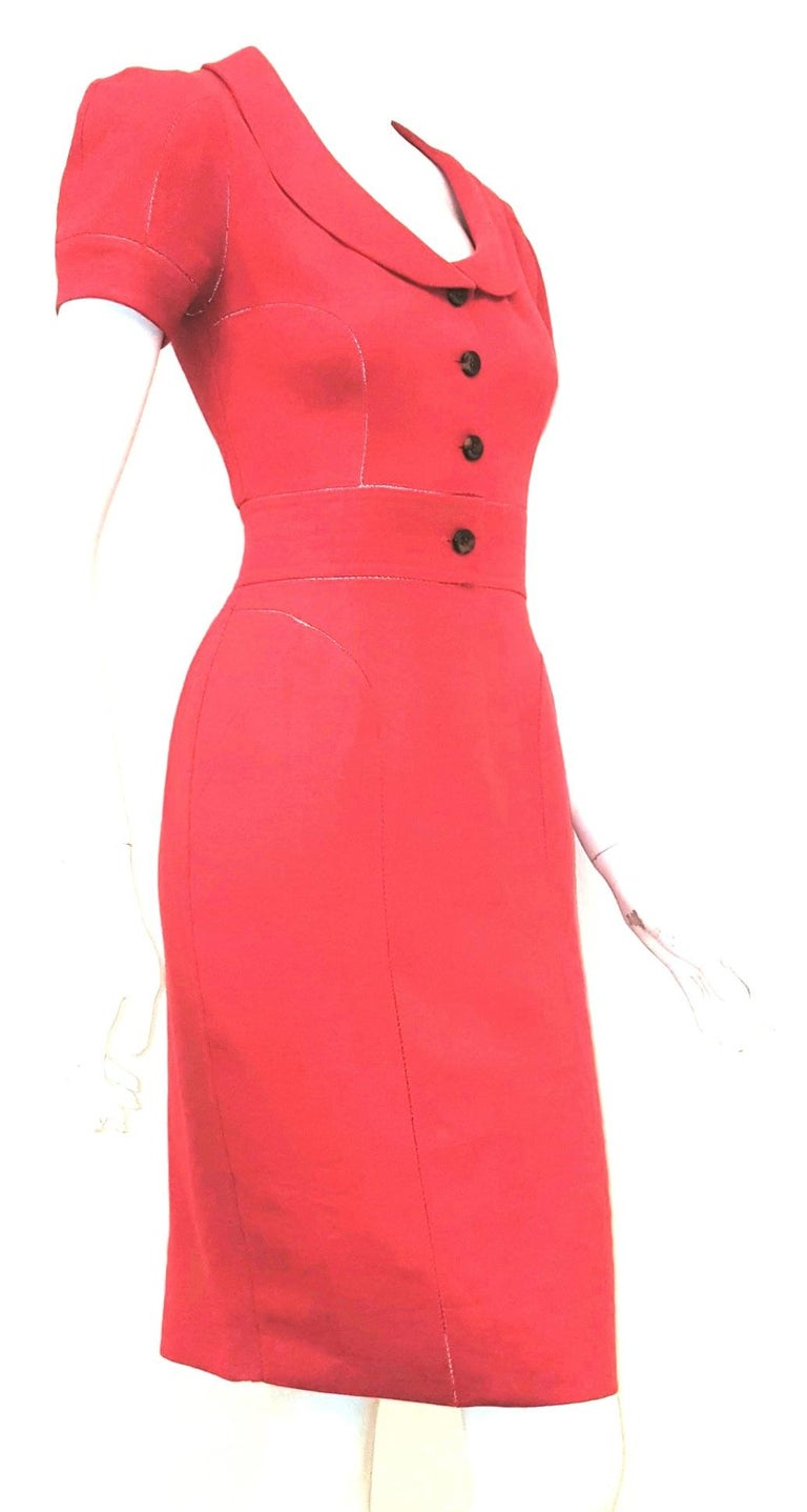 Fendi red linen dress with zig-zag open stitching is meticulously constructed!  This dress has a low cut round collar that terminates with opening and 4 Fendi buttons for closure at front.  The short sleeves are slightly gathered at shoulder