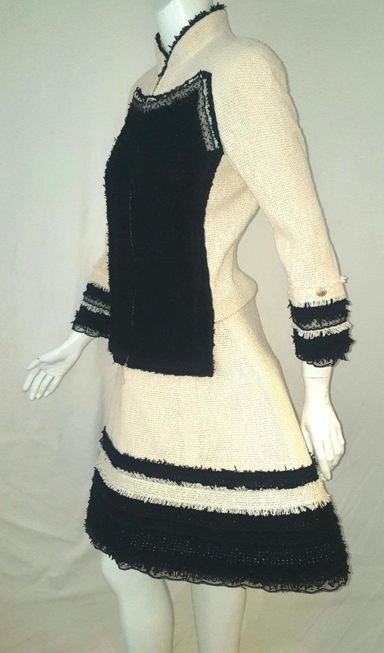 Chanel ivory and black trim fringe and ruffled lace on both the jacket and skirt.  This fabulous jacket features a tailored fitted silhouette with an up collar w/ black fringe & zipper closure. 2 front plaquettes in black boucle fabric framed in