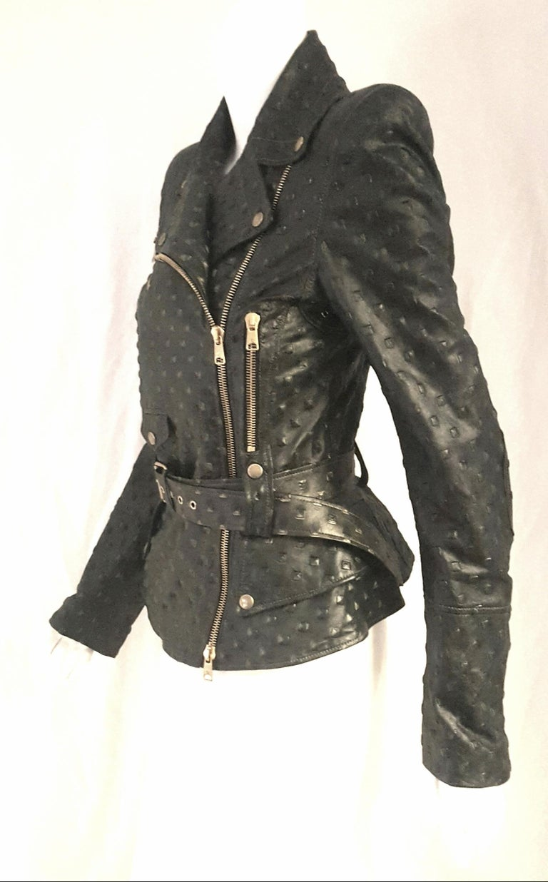 Alexander McQueen stamped black leather has been printed with a specific technique that causes irregularities in the color tones as this black jacket that has greenish hues throughout making it one of a kind.   Zips and snaps dominate the edgy biker