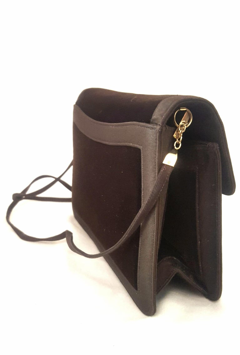This Judith Leiber brown velvet and satin shoulder and clutch bag is lined in brown satin with one side slit pocket and one zippered pocket.  Single flap closure with magnetic snap is found at front.   This bag also contains one exterior slit pocket