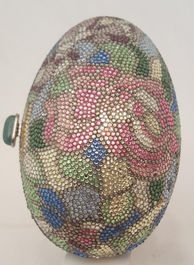 Add to your collection this highly sought after Judith Leiber Egg with Swarovski crystal minaudiere bag crafted from individually placed multi color crystals. This egg with a floral theme contains pink, lavender and white flower on a mosaic