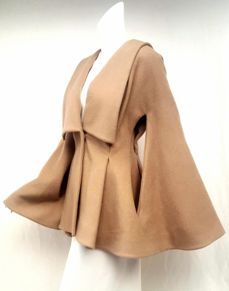 Alexander McQueen Camel hair jacket with shawl collar is gathered at the waist with wide pleats at front and back for that cinched and flared look.   Savile Row trained Alexander McQueen was a fashion visionary whose shows fused radical theatrics