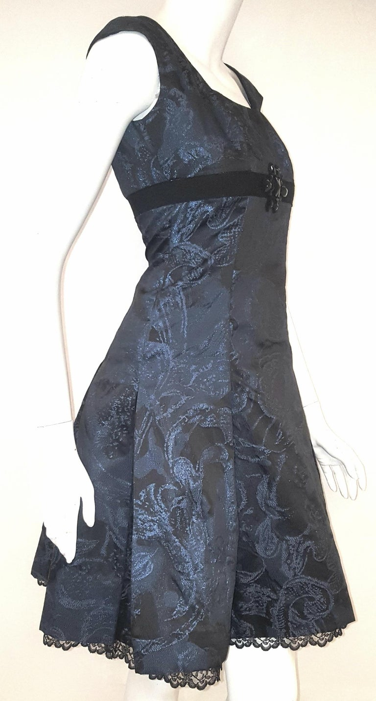 Carolina Herrera black and blue metallic brocade dress is enhanced with a black grosgrain band and a beaded flower at center of bustline.  Sleek in silhouette and texture, this tailored A-line dress features a coquette hemline with a lace petite