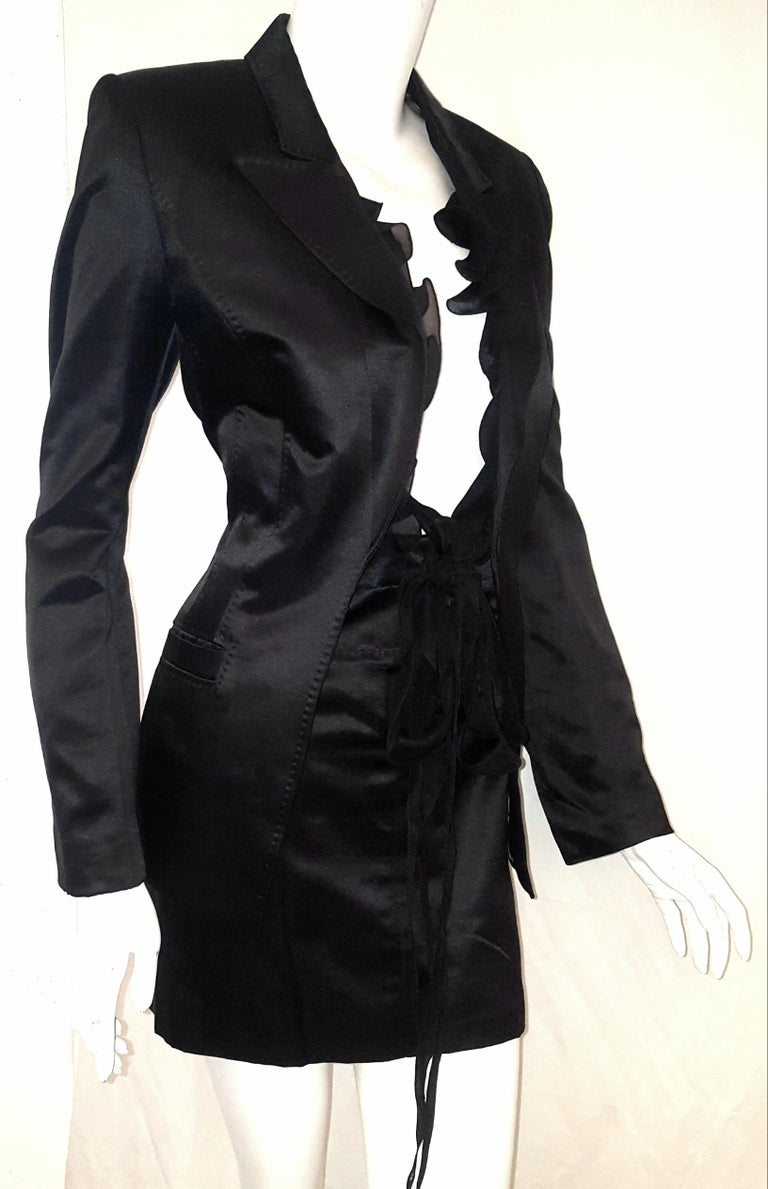 Roberto Cavalli black satin silk and cotton with silk ruffles that can be tied in a bow, for closure or just left loose.  This satin suit has 5 concealed Roberto Cavalli buttons on each cuff.  For closure , the skirt has 2 hook and eye and one