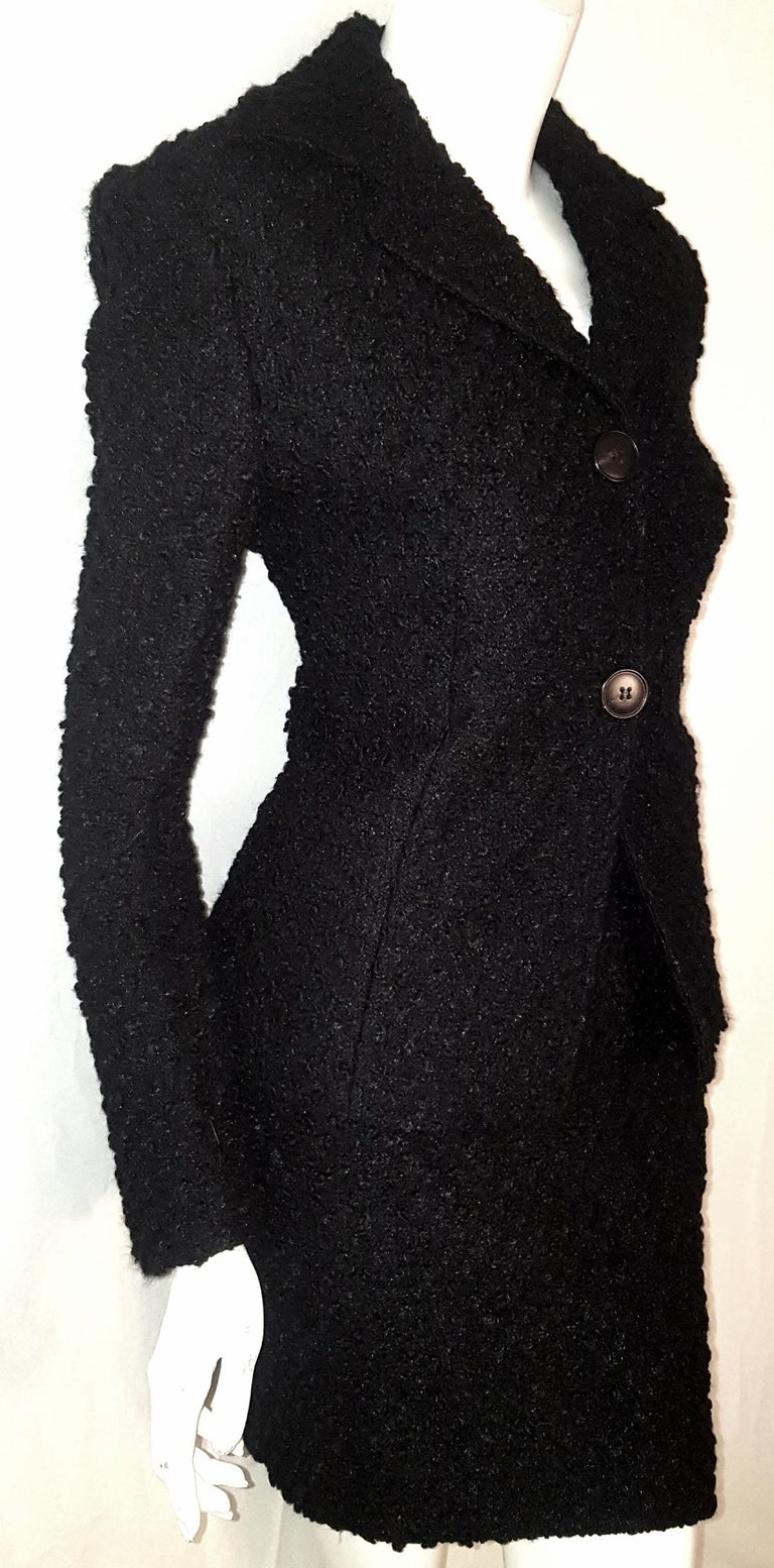 This always appropriate black cotton and wool tweed skirt and jacket suit from Dolce & Gabbana features a notch collar.   Two button fastening for closure,  at front.  This jacket has a fitted waist and long sleeves with 3 buttons at cuff.   The