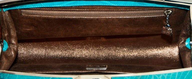 Judith Leiber turquoise genuine crocodile clutch features a silver tone metal frame and a large crystal on the flip clasp for closure. The interior is lined with metallic pewter tone leather.  Two pockets can be found in the interior one slit pocket