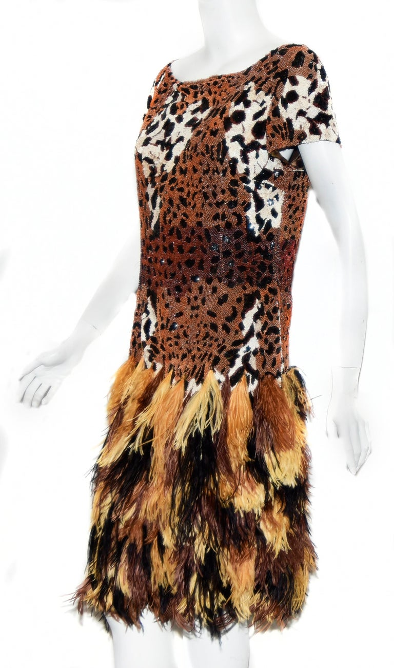 One of the best examples of Naeem Khan's magic couture is this cocktail dress with ostrich feathers dyed to match the leopard print where the spots are created from stacks of sequins!  Done with Khan's skillful hand, this short sleeve, scoop