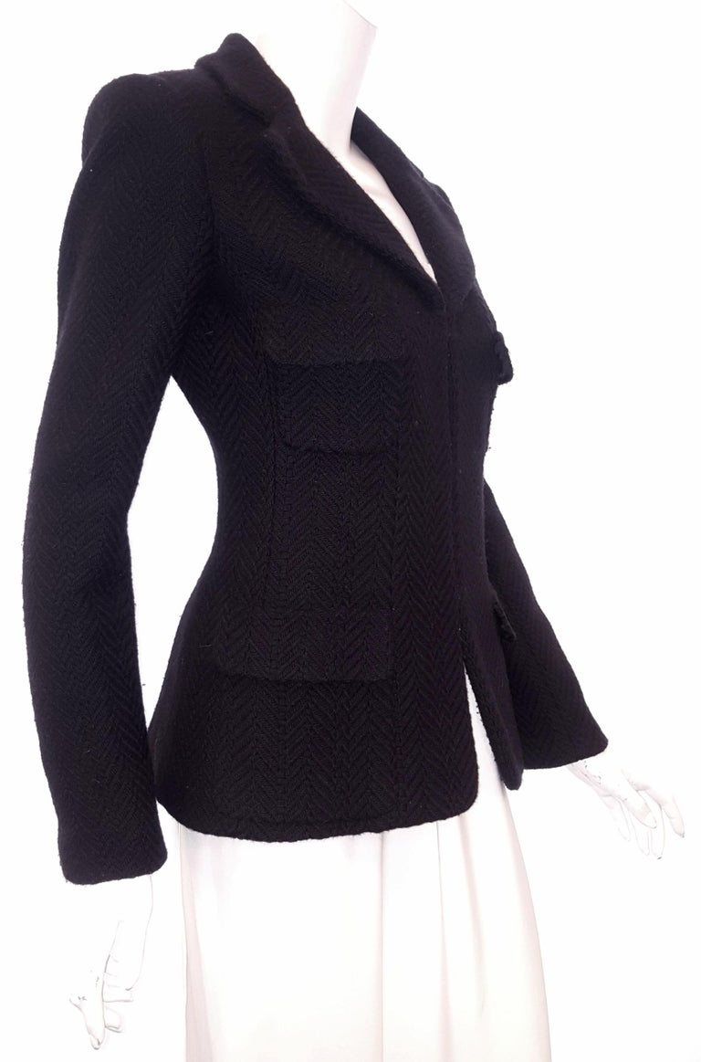 Chanel black wool 2006 Fall Collection classic Chanel herringbone woven tweed jacket incorporates a notch collar.  With four flap pockets at front, and padded shoulders, this jacket is a little bit retro.  Three black buttons, each with a silvertone