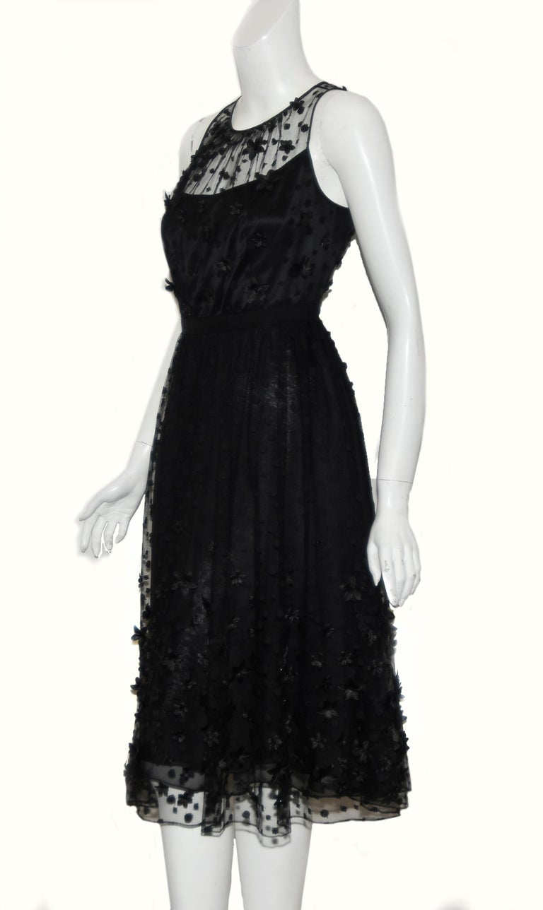 Carmen Marc Valvo black tulle with embroidery details throughout includes 3D flower appliques around bodice and hem of dress.  This dress contains illusion shoulders and back,  giving the concept of floating flowers.  For closure, a zipper and hook