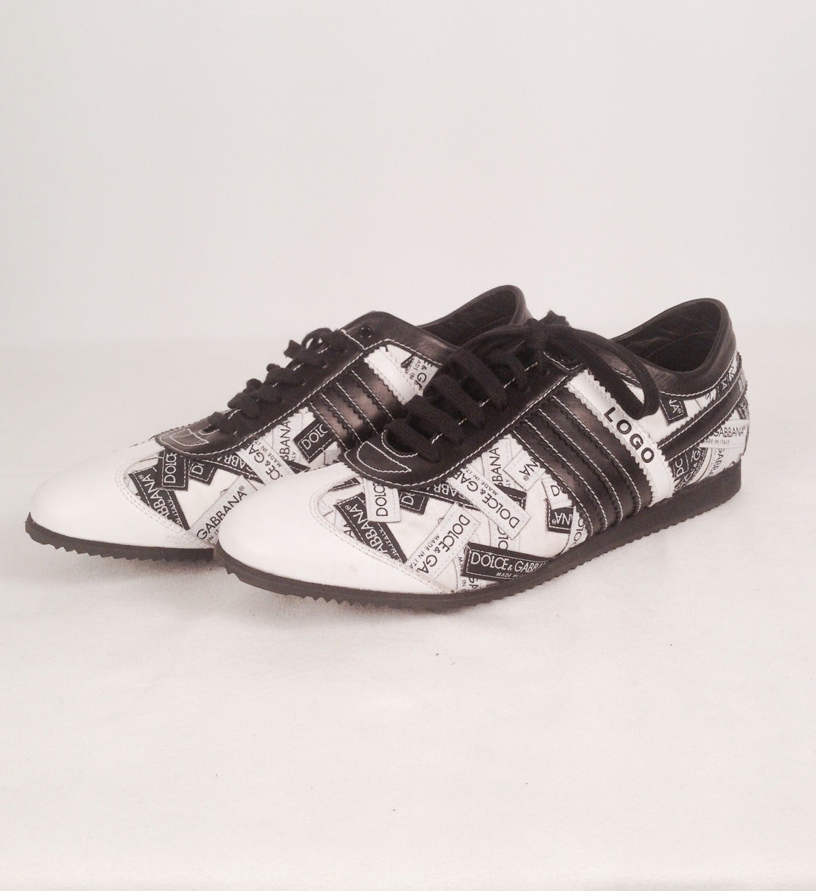 "Logo Sneakers literally celebrate the success that Dolce & Gabbana has achieved in the world of high fashion.  Literally emblazoned with black and white ""tags"", shoes have five strips....four black and one white proclaiming ""LOGO"".  A must for any"