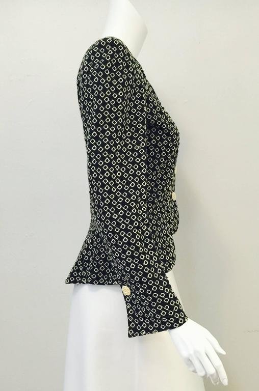 Black and White Eyelet Skirt Suit shows why Emanuel Ungaro's couture house is considered one of the finest of the late 20th Century.  Suit features scallop hemmed, peplum jacket that is perfectly paired with a straight skirt.  Slightly rounded and