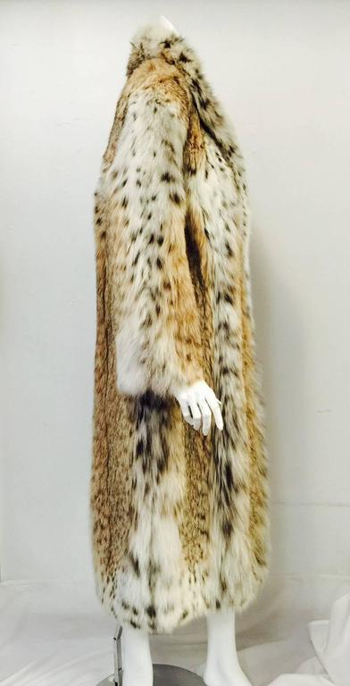 30% OFF!  Luxurious Full-Length Coat is equally at home in St. Moritz, Vail, or New York.  Features natural lynx, two pockets and adjustable collar.  One interior pocket.  Fully lined in deep champagne satin.  Secured by three furrier hooks and