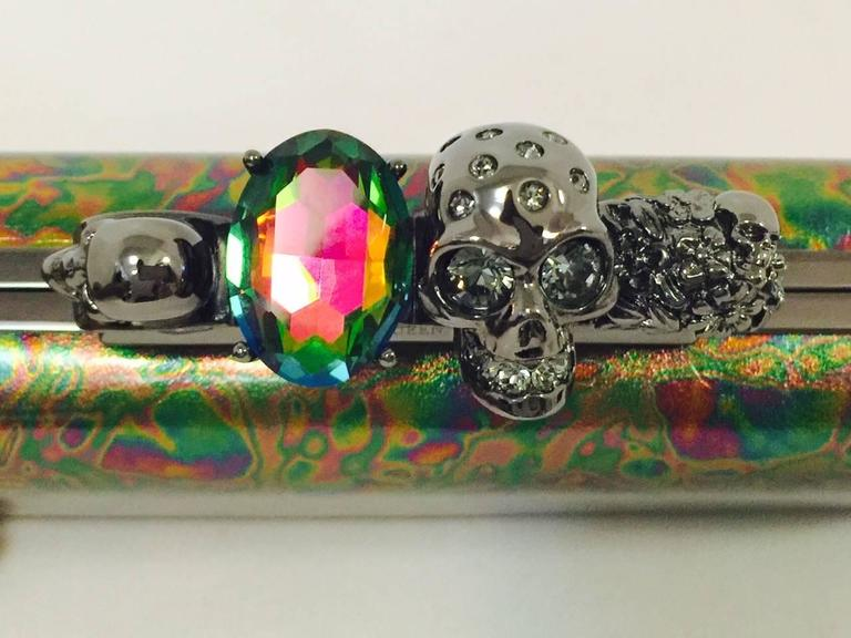 Oil Slick Knuckle Duster Box Clutch is an instant classic and highly desired by connoisseurs of Alexander McQeen creations!  Featuring the iconic knuckle closure, this stunning clutch has Swarovski crystal embellished skulls and a stunning large