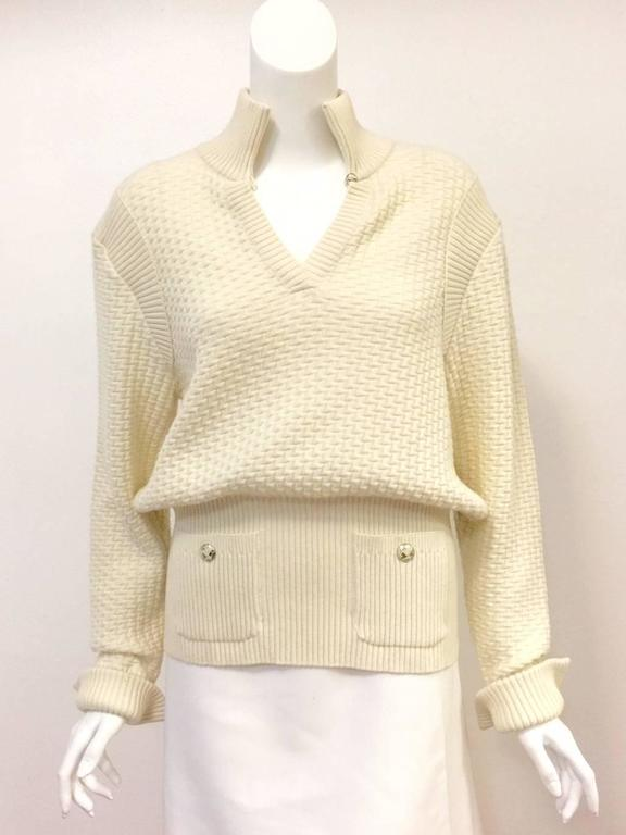 100% Ivory Wool Pullover Sweater proves that Chanel is much more than mere boucle skirt suits and quilted handbags!  V-Neckline features single button closure and stand up collar  design.  Generous proporations define the sleeves and body.  Sleeves