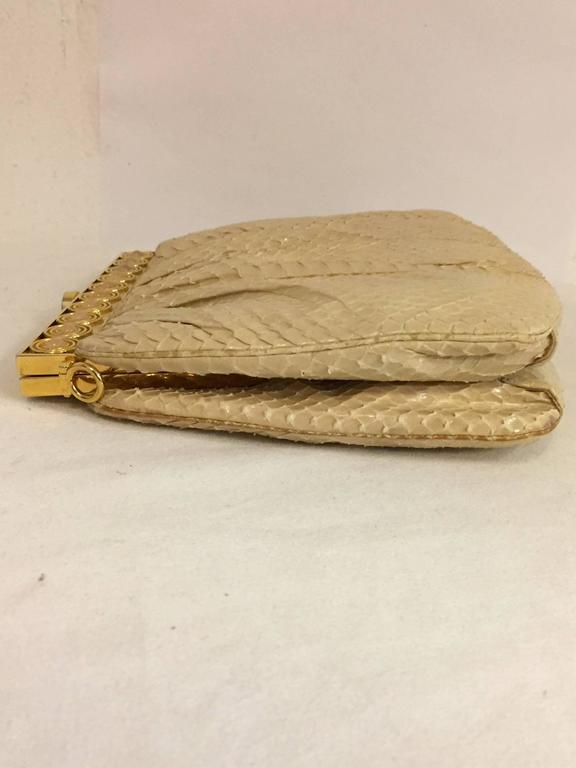 Stylish pleated cream colored skin, tonal stitching with gold tone hardware at closure.   The snakeskin strap is also cream color and can be removed.  Beautifully constructed in 1986 in the authentic Judith Leiber fashion.  The inside has one