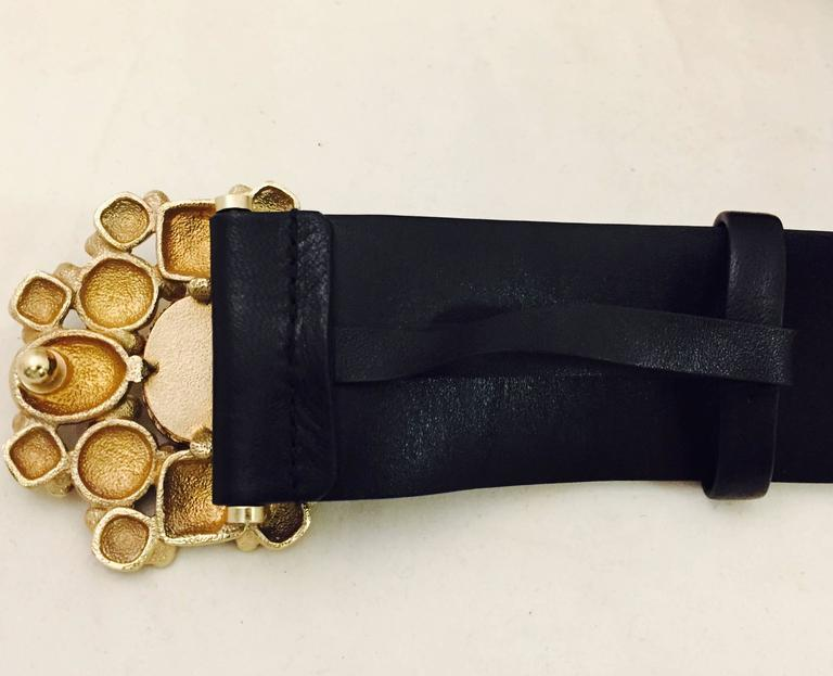 Chanel black leather belt with its eminent belt buckle medallion with Gripoix stones on antiqued gold tone flower design.  This stunner is a work of art that is wearable and unique.  The Gripoix stones are Red, Black and Blue with the CC logo on the