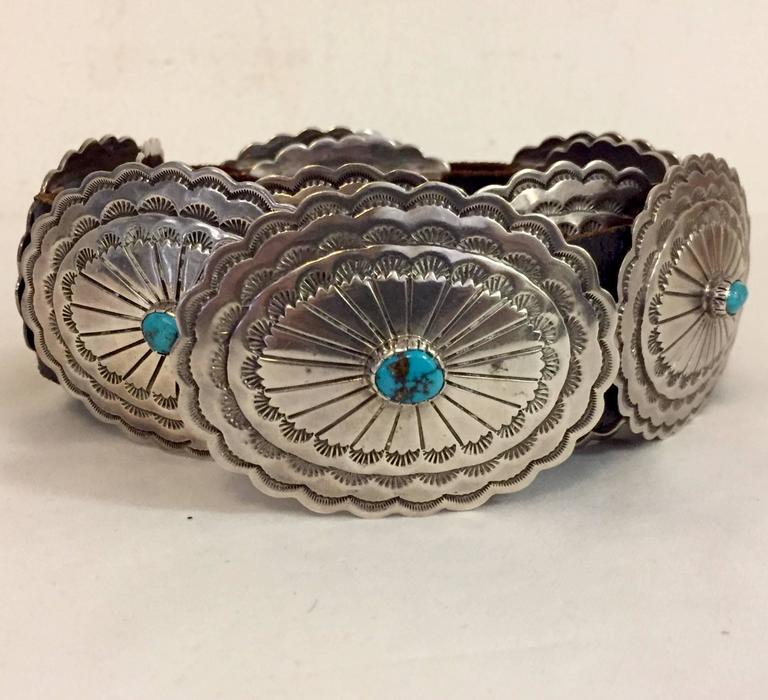 "A beautifully crafted concho belt featuring 11 scalloped edge, heavily engraved Sterling Silver stations, each centered with a bezel set turquoise matrix stone.  These slide along a 1.5"" piece of dark brown leather measuring 34"" long.  Each Sterling"