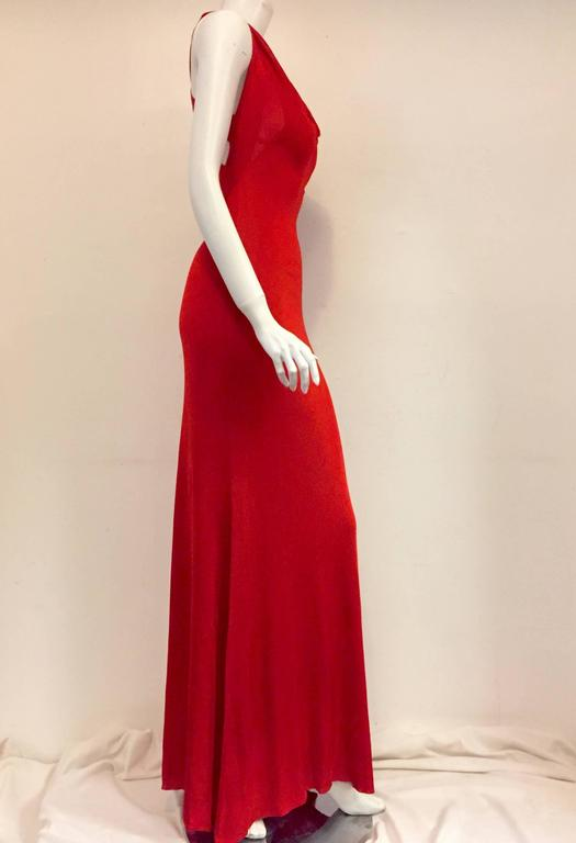 Fit for a siren, this striking Red Alexander McQueen gown features crisscross straps on back and scalloped neck in front. Crafted from luxurious 100% viscose this gown celebrates the natural curves of a woman and promises an unforgettable,