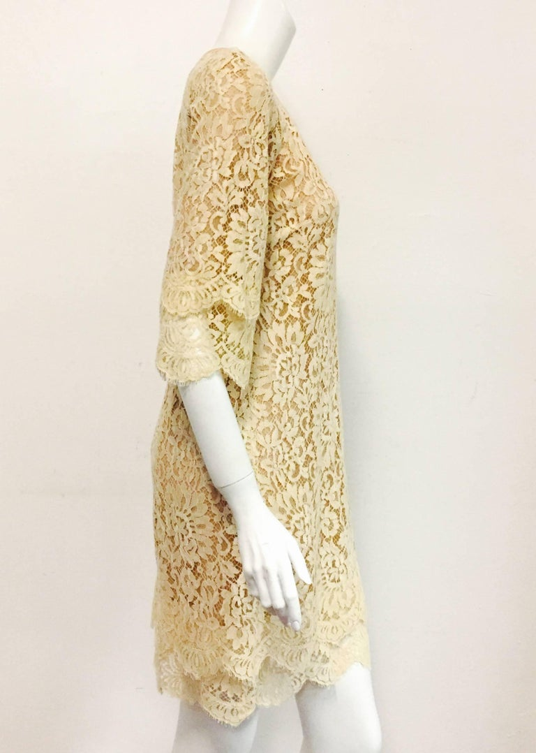 Made in Italy, this Michael Kors Beige Lace dress has a silk border around the scoop neckline and three-quarter raglan sleeves.  Optional silk ribbon may be used to cinch this ode to femininity at the waist for a more tailored look.  The 3/4 sleeves