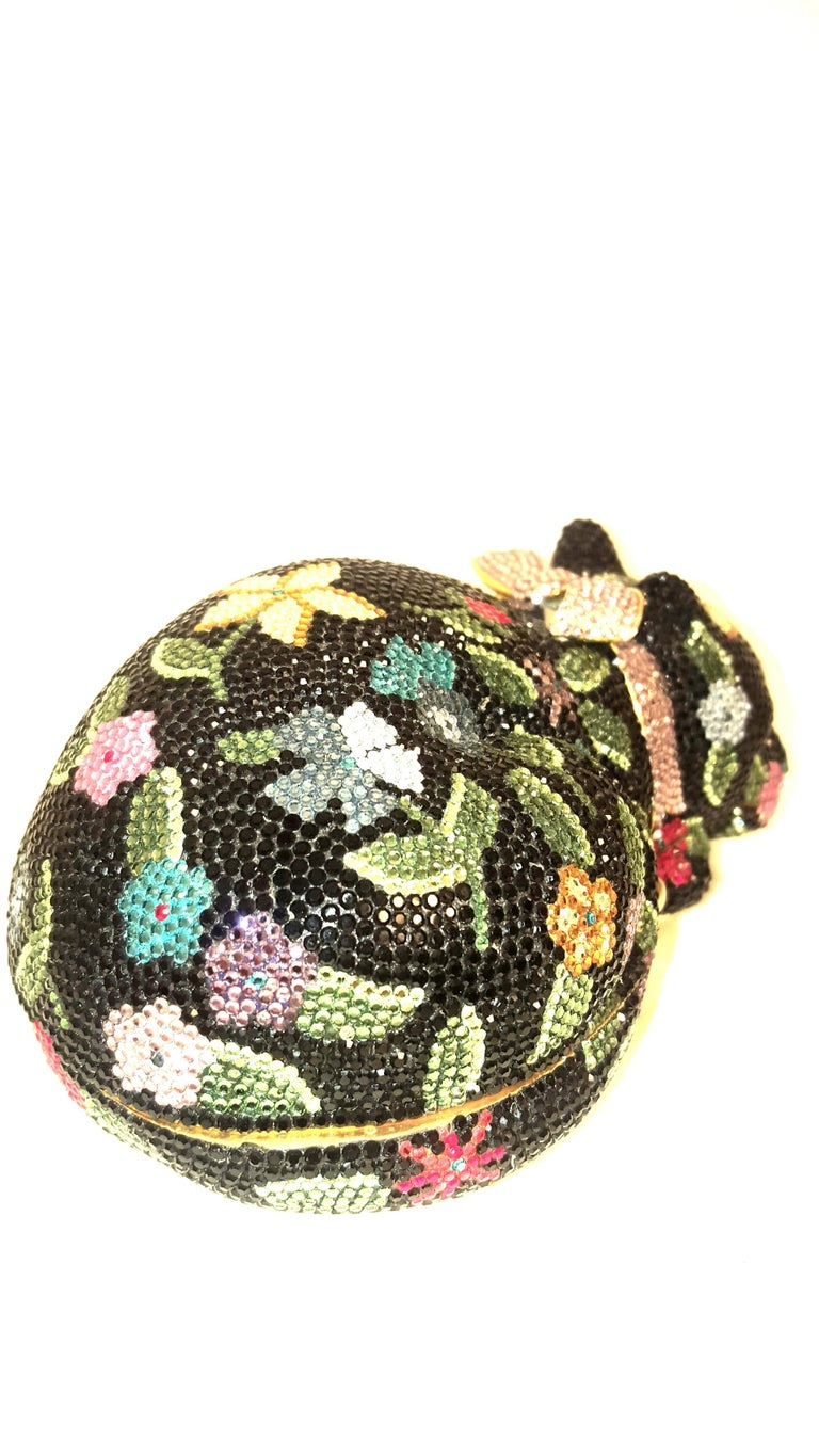Judith Leiber minaudière features the form of a bejeweled sleeping cat with a bow around its neck. The hard clutch is covered all over with mini Swarovski crystals with black background and multi flowers floating around in shades of yellow, red,