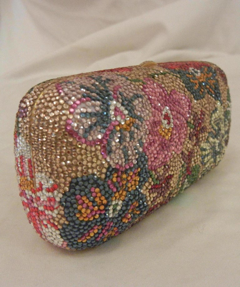 Judith Leiber Swarovski crystal floral print mini minaudiere with gold tone tassel rope bag is in excellent condition. Multicolor floral print swarovski crystal exterior trimmed with a yellow gold corded rope tassel detail. Top button closure opens