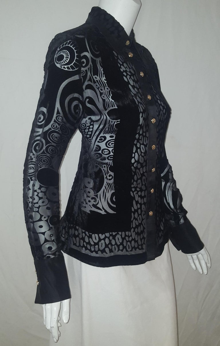 Versace black silk blend with cut velvet arabesque design throughout with long sleeves is pure Versace.  The shirt collar is trimmed in black silk and lined at the back of the collar, also, in black silk.  The top switches from see through to solid