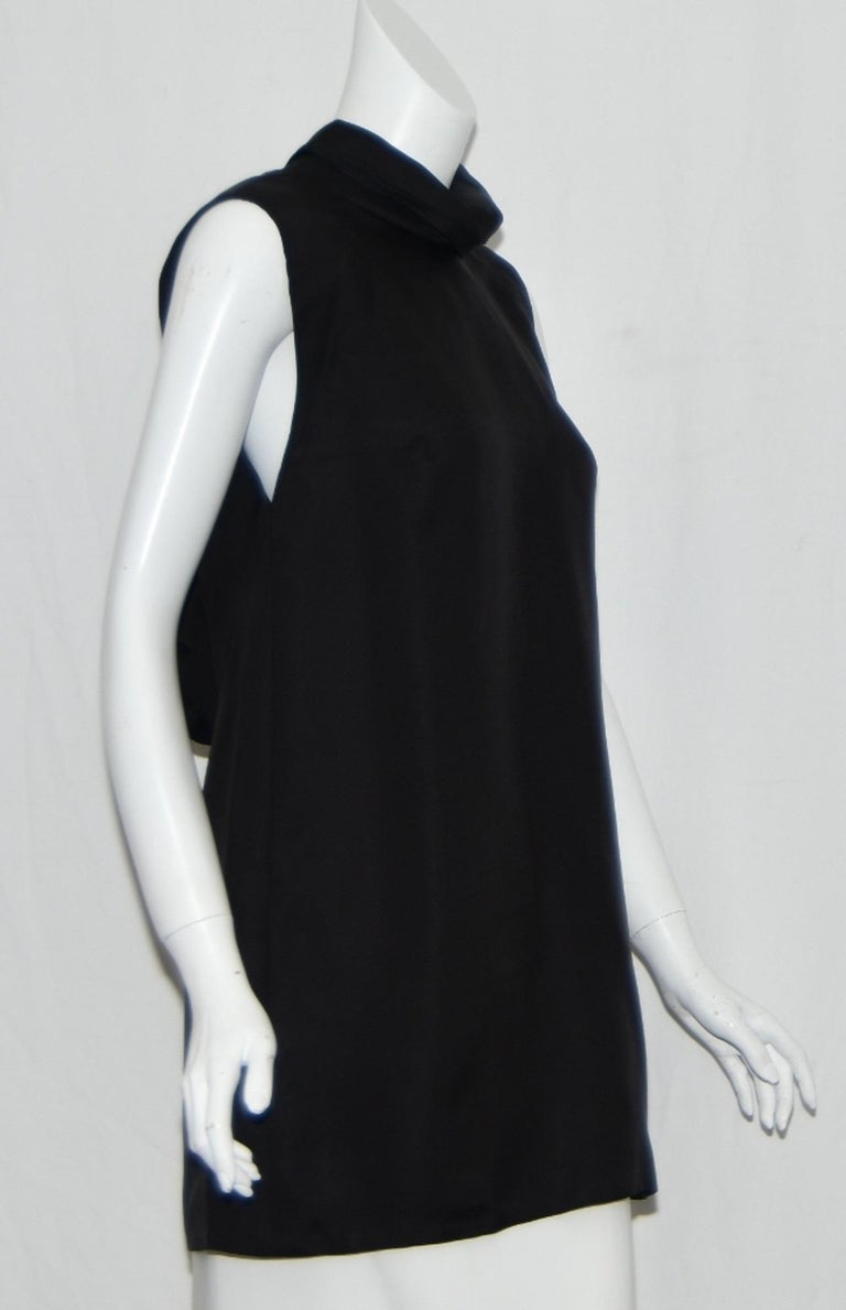 Gucci black mini dress with ruffle flounce detail and that spectacular open back, that sauntered down the Gucci runway a true depiction of minimalism.  It's simple style, straight lines, and clean shape, exude sheer minimalistic elegance.   It