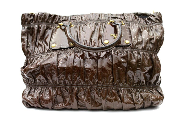 Comfortable and functional this is a bag for everyday. It is made with a vernice leather. The color is ematite with gold hardware. Internally it is lined in cloth with Prada logo. Very good condition.