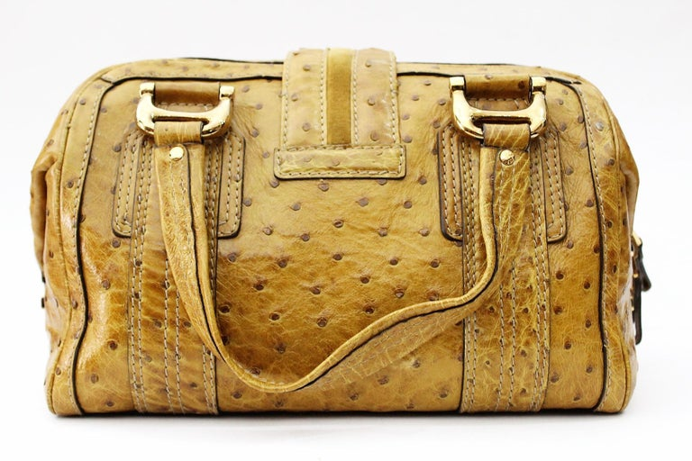 Gold ostrich Gucci Aviatrix Boston bag with antiqued gold-tone hardware, dual flat top handles, Hysteria logo accent at front face, contrast stitching throughout, brown suede lining, three pockets at interior walls; one with zip closure and two-way