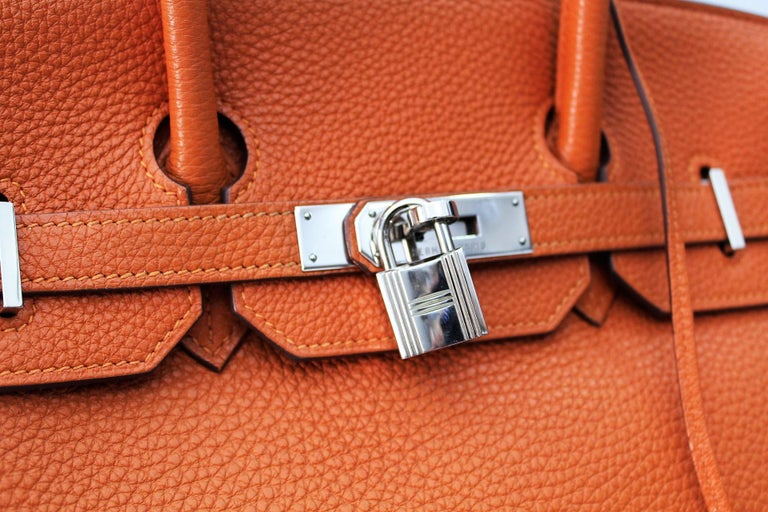 This elegant Birkin bag is made of Togo calf leather elaborately worked in orange. The bag features leather handles, a crossed flap with strap closure and a revolving palladium padlock, lock and a hanging clochette with keys. These open onto a
