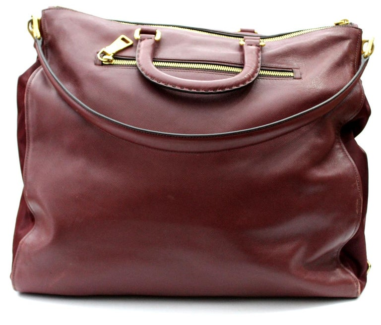 Prada model shopper bag. In a fabulous burgundy tint, in leather with gold trim. Wearable by hand through the two upper handles or on the shoulder thanks to the removable shoulder strap. Large and internally very spacious, with pockets. The bag is