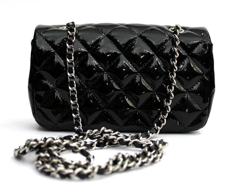 Wonderful Chanel Mini Flap in black patent leather and silver hardware. Equipped with a long chain and leather shoulder strap.