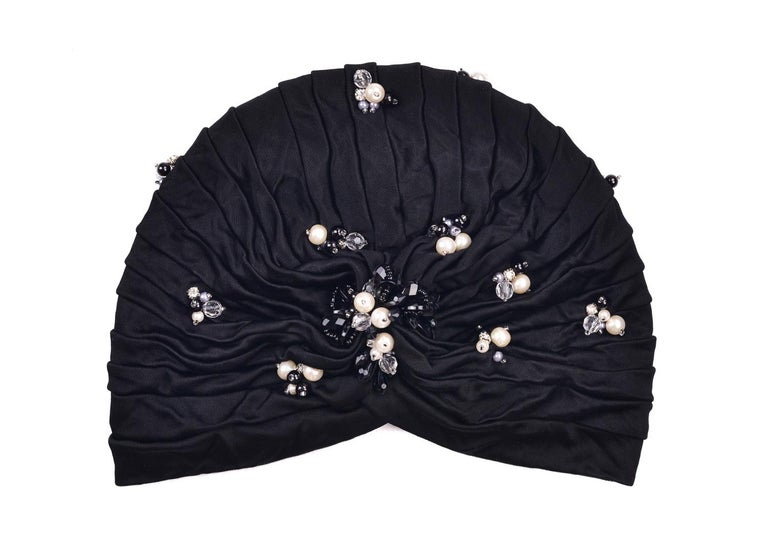 Be one with artistic rarity with Roberto Cavalli's Soft Pearled Turban. This head piece features sleek pearls, chiseled transparent stones, and grey and black micro pearl appliques across a tiered body. You can wear this evening classic before or