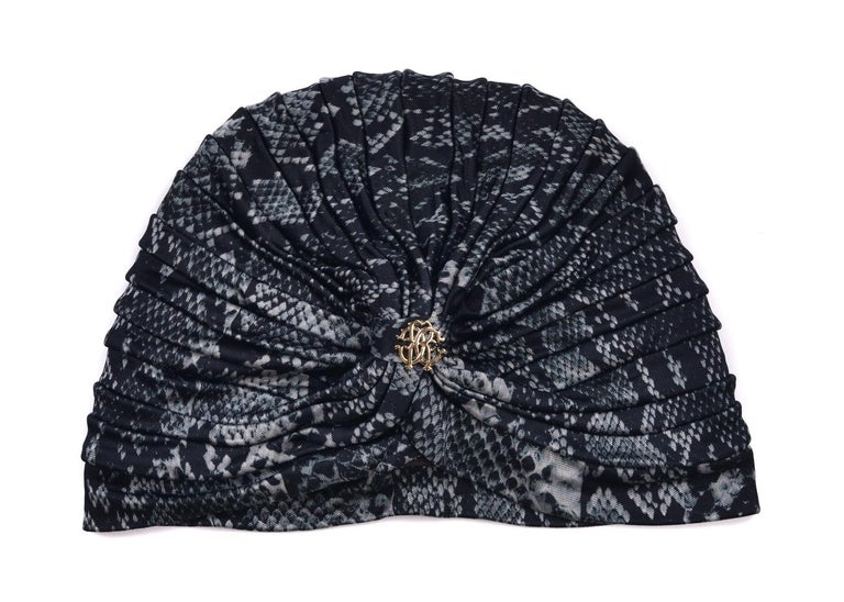 Be one with your wild artisan side with Roberto Cavalli's Snake Print Tiered Turban. This head piece features a grey and black snake print, centered gold RC Logo, and uniformly tiered body. You can dawn this evening beauty before or after that