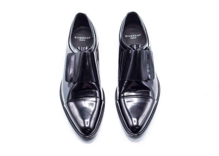 Classic black oxford silhouette from fashion house Givenchy to up your dressy wardrobe. Pair with any dress bottoms and dress shirt for that classic look. Monk Style Strap over With a Hidden Zipper to make this Shoe a classic. Metal Stripe on Heel