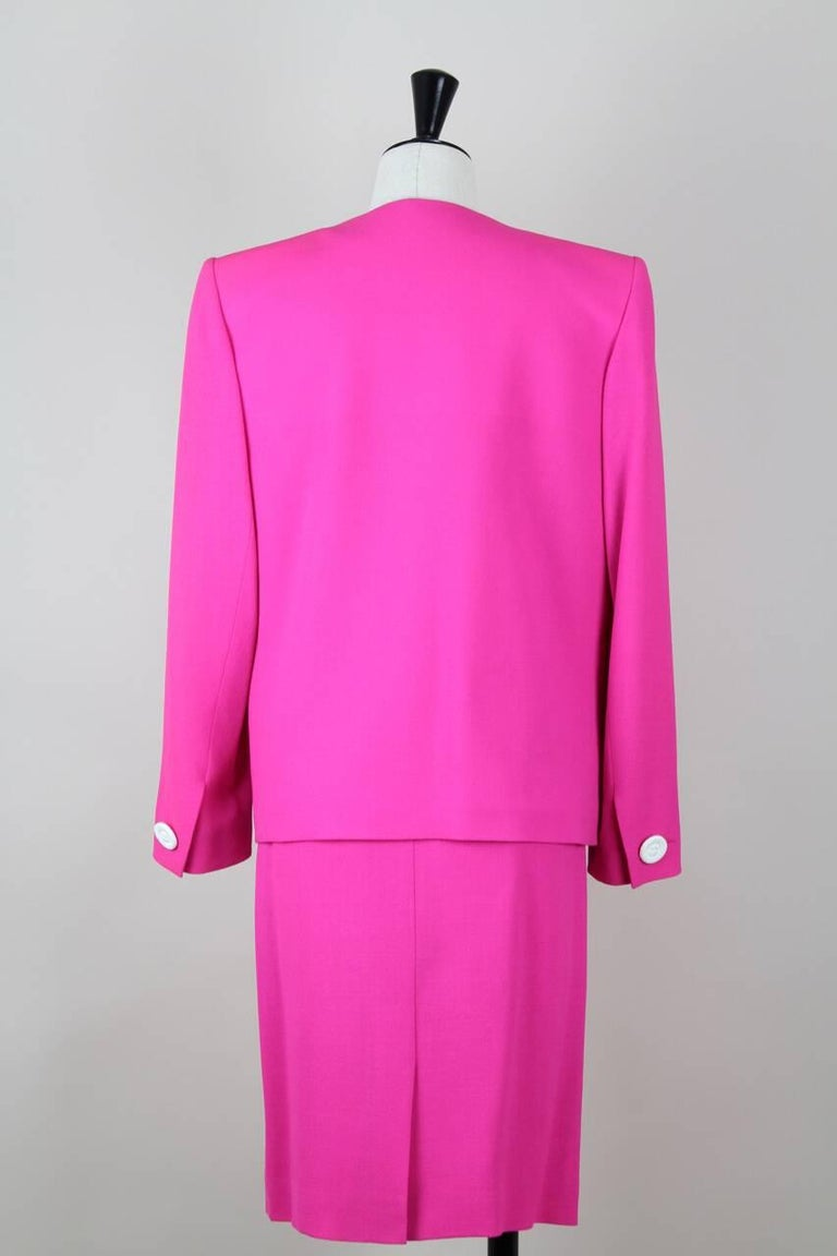 This jacket and skirt suit is made from a lightweight hot pink wool blend crepe. The collarless jacket has a box cut with shoulder pads, long sleeves with buttoned cuffs and two lower front lined patch pockets with an eye-catching white