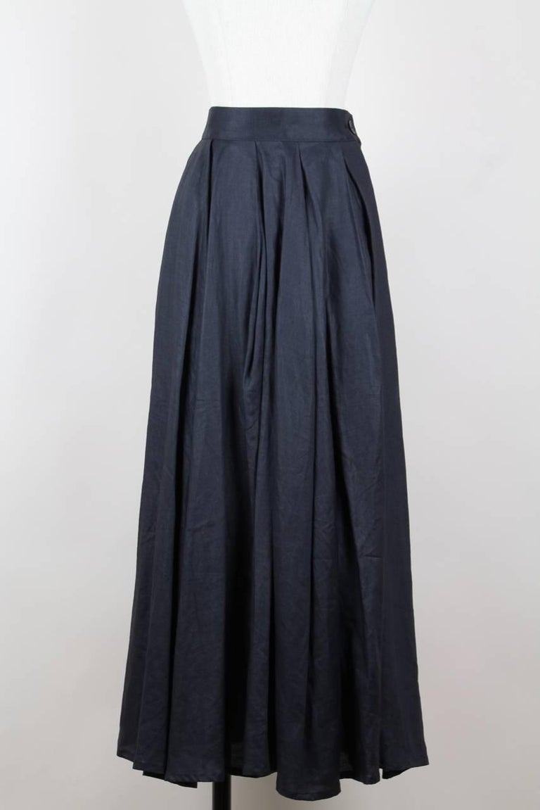This feminine maxi skirt is made from charcoal grey crisp linen. It features a waistband and is draped in the back creating an asymmetric hemline. The skirt is unlined, closes on the left side with a hidden zipper and a button and labeled