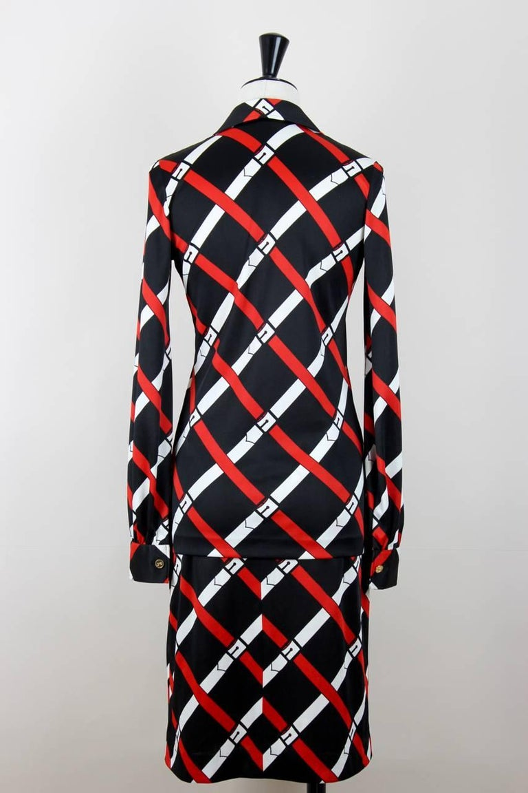 """This jersey blouse and skirt set features a signature trompe l'oeil belt print in red and white on a black background with the iconic """"R"""" printed in between. The blouse has an open collar and long sleeves with buttoned cuffs (gold-coloured """"R"""" logo"""