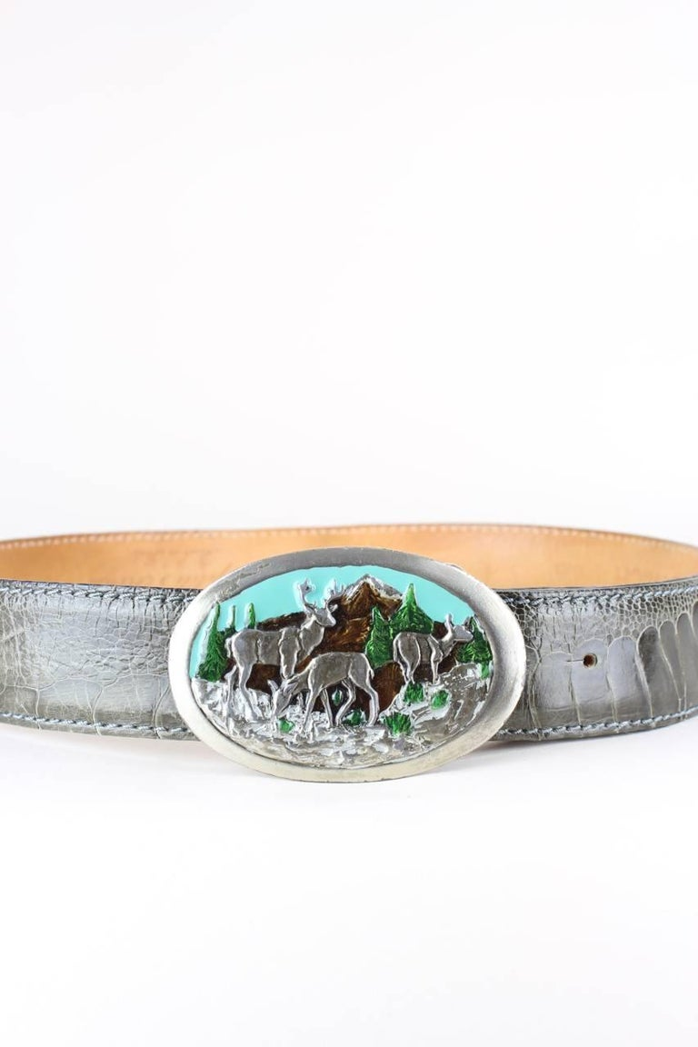 This lovely heavy and solid oval-shaped belt buckle is made from silver-toned metal. The buckle features an enamel design of deer in the mountains with turquoise sky, brown mountains and green firs and grass. The back has fine engraving details and