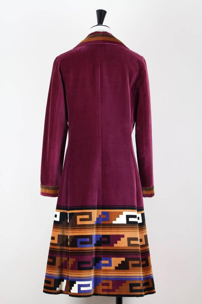 This outstanding 1970s Roberta di Camerino coat is made from soft ruby velvet with a beautiful Aztec print in burnt orange, brown, caramel and vibrant blue. It features a four point collar, darts at the bust, two side seam pockets and flares
