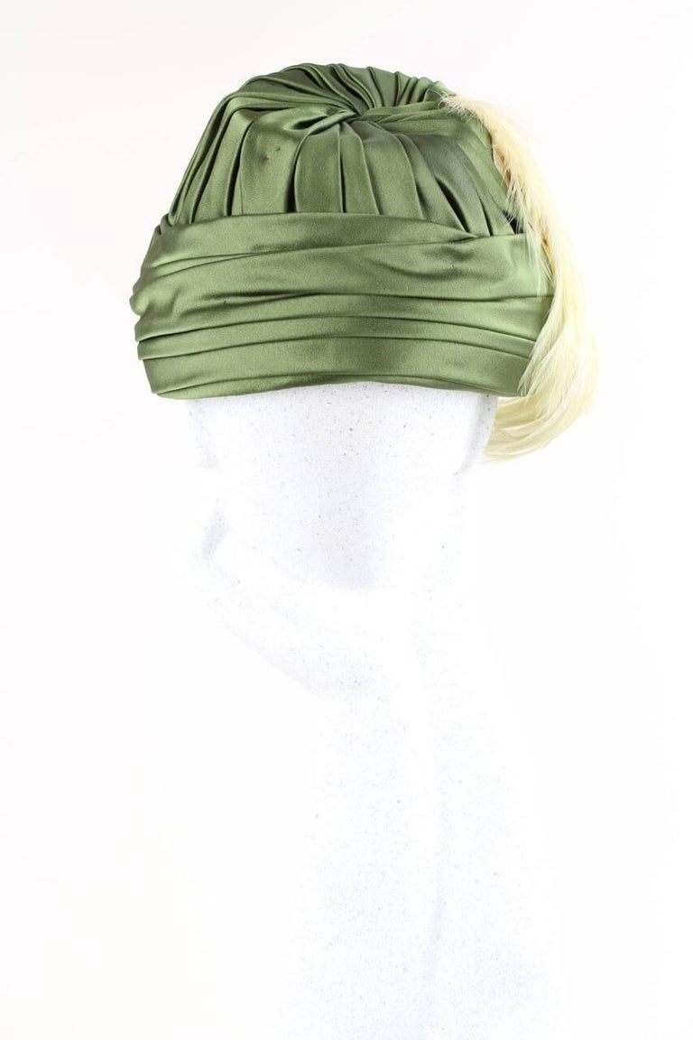 Fantastic 1950s numbered, possibly haute couture, olive green silk satin vintage hat adorned with peach feathers at the right side. Beautiful details of pleating, folding and twisting! The hat has an interior olive green grosgrain ribbon band, is