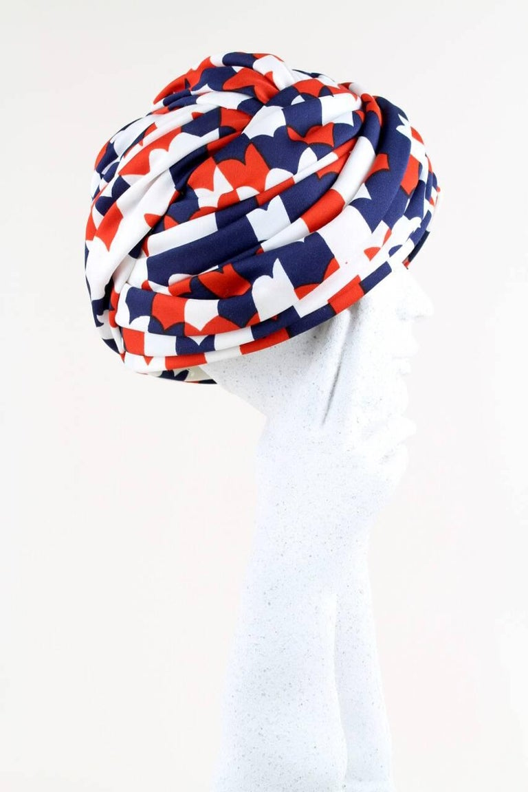 This beautifully draped 1950s/1960s turban hat is hand-made from a soft fabric with a lovely stylized heart print in navy, cherry-red and white. Gorgeous details of pleating, folding and twisting. The hat has an interior cream grosgrain ribbon band