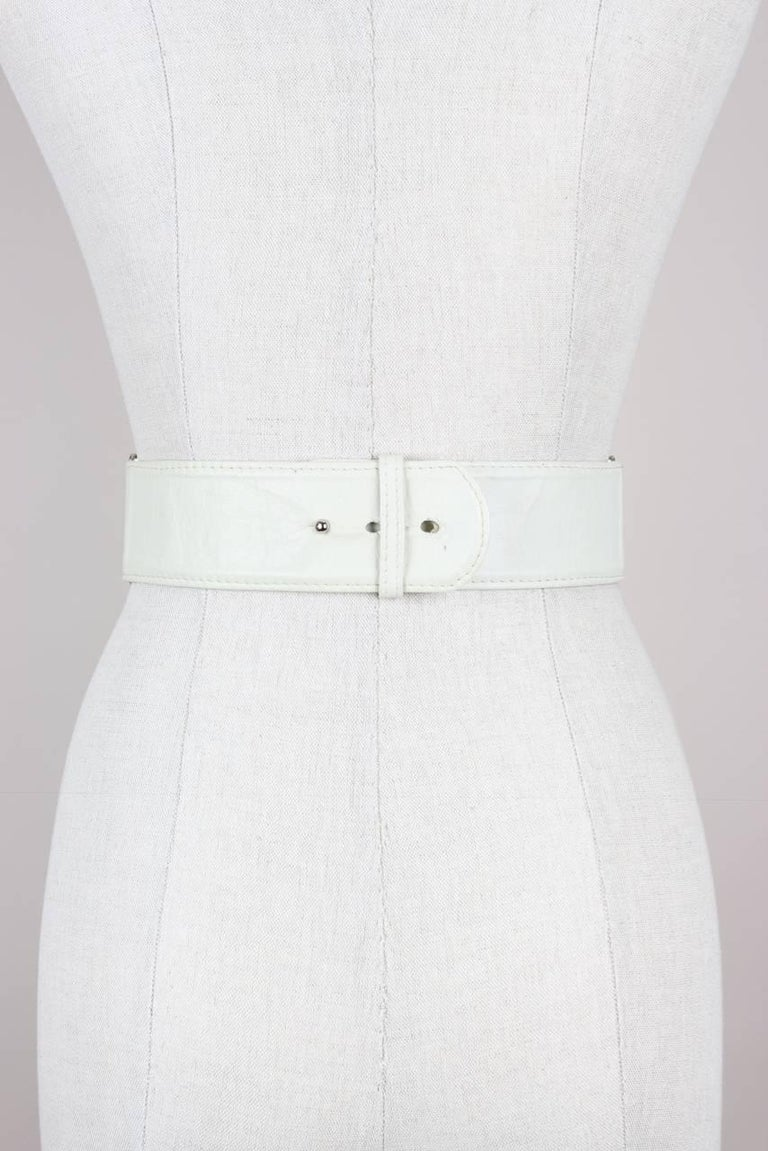 """Heavy silver-tone embellished mesh belt with white crystal rhinestones and off-white smooth leather ends. The belt features a pushpin fastening and is marked """"Gianni Versace"""" and size """"75"""" inside the belt. A small adhesive label"""