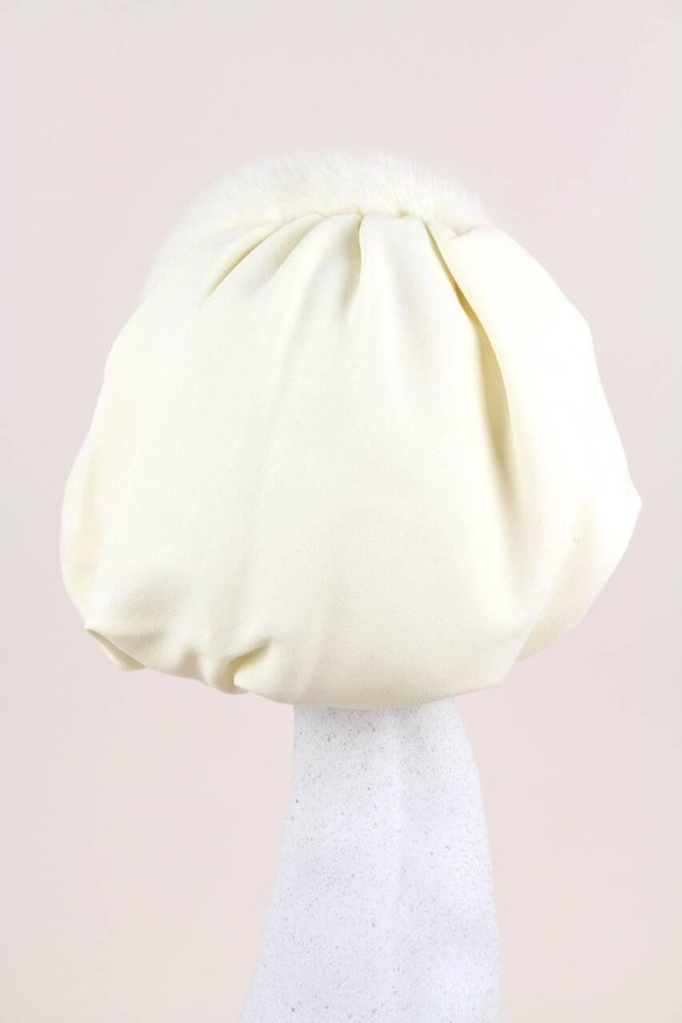 This rare and unusual bonnet-style hat is entirely made by hand of an ivory fabric that feels like a silk crepe and soft and supple real mink fur of the same colour. It comprises of a stiffened mink fur covered headband hat and a soft sewed on