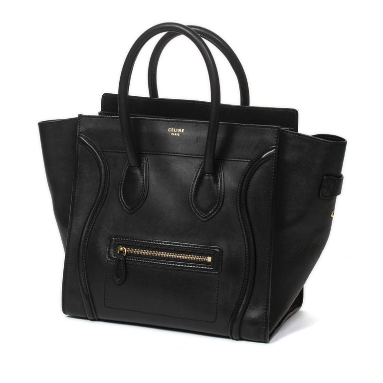 "Luggage Tote Mini in black leather with frontal zip pocket, gold tone hardware. Top zip closure. Leather lined interior with one zip pocket and 2 slip pockets. Production number F-SA-0132/ F-CU-0152. Dustbag included. Stamp ""CÉLINE PARIS"" ""MADE IN"