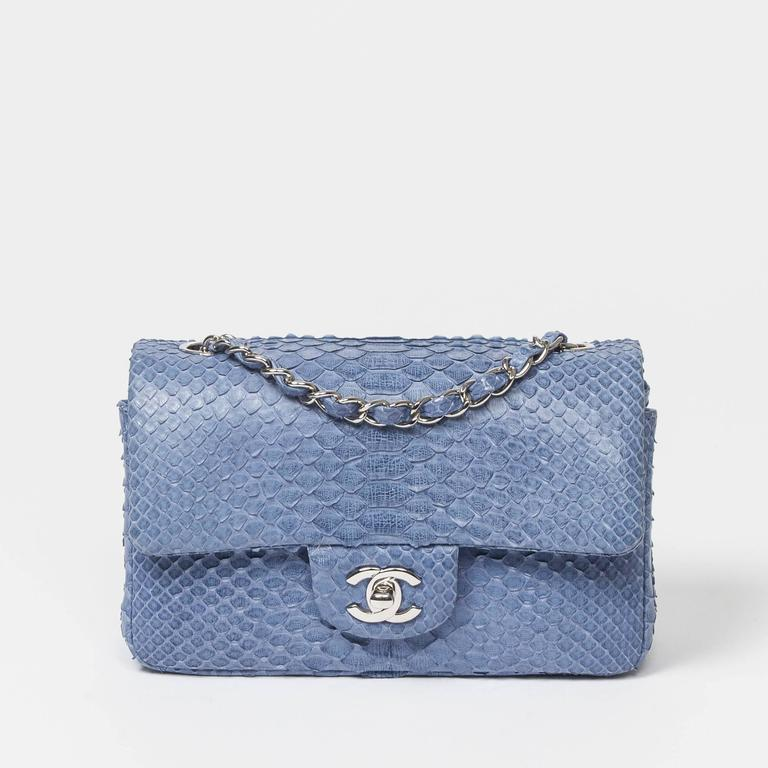 "Mini Flap in powder blue python skin, silver chain strap interlaced with python and CC turnlock. Back slip pocket. Denim blue leather lined interior with one slip pocket and one zip pocket. Engraved metal plaque ""CHANEL"" ""MADE IN FRANCE"". Box and"